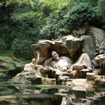 Sculpture of man and tiger lounging by natural spring in forest, China